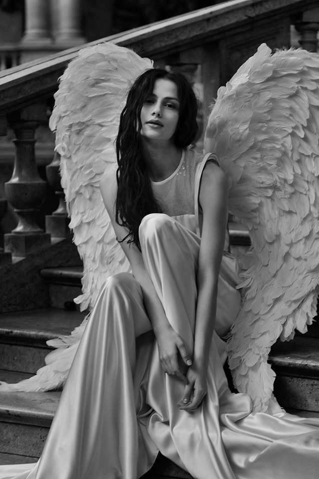 black and white photo of a girl with wings on her back sitting on a staircase