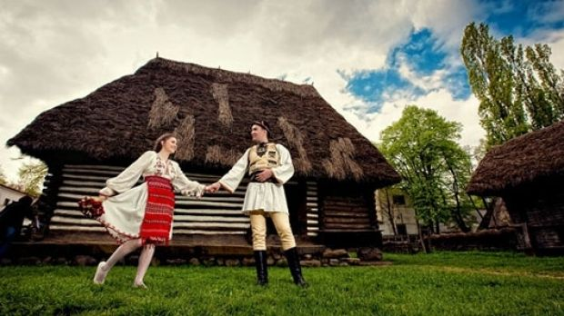 Photo of Romanian man and woman in traditional clothes in front of house
